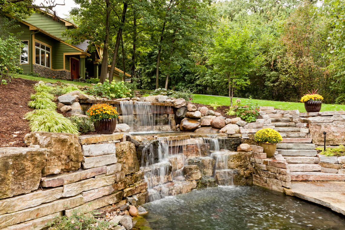 backyard waterfall with flowers and green grass