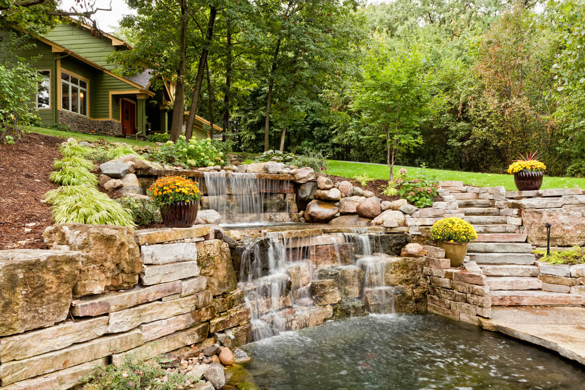 water fall in back yard with green grass