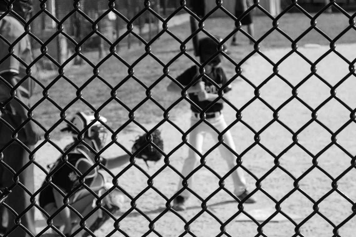 boy playing baseball behind a fence