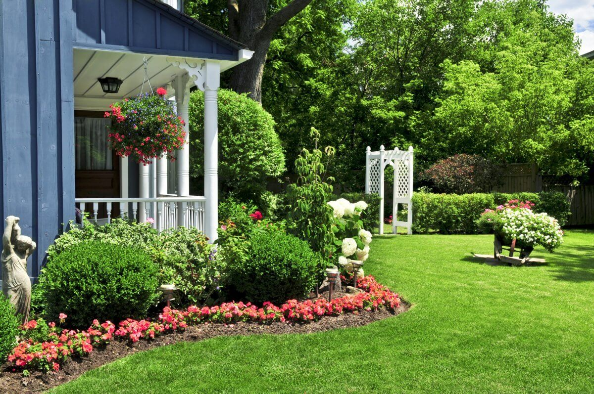 back porch with white railings and flowers and scrubs