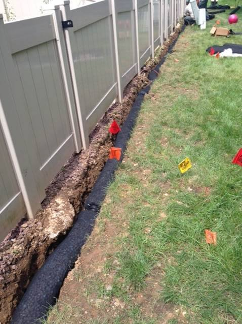 french drain installation along a white fence