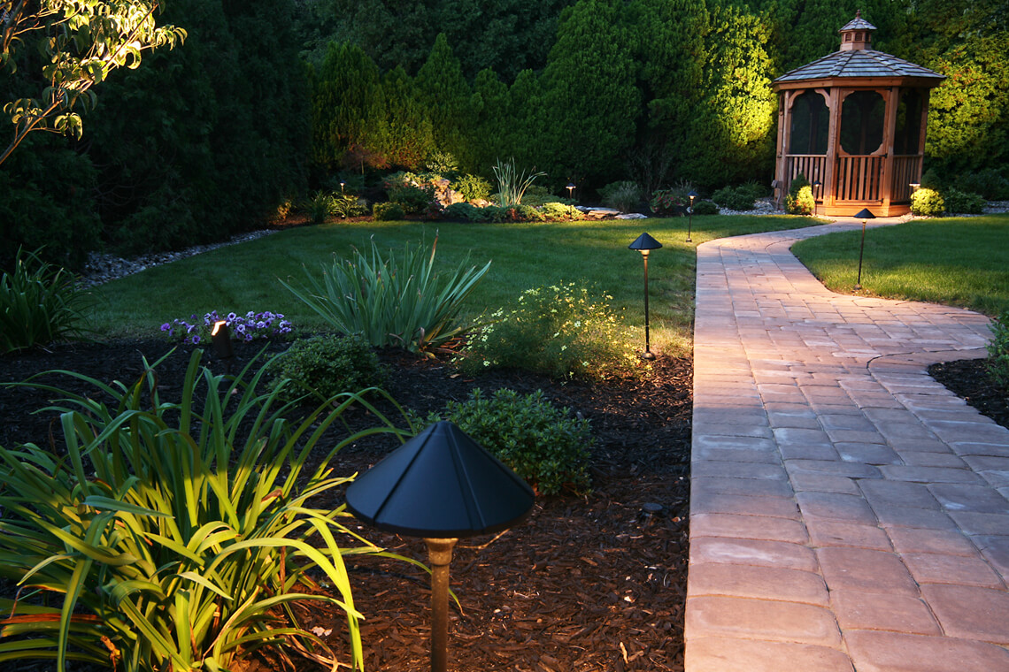 Light red stone pathway to gazebo with pathway garden lighting next to green plants in brown mulch and green grass