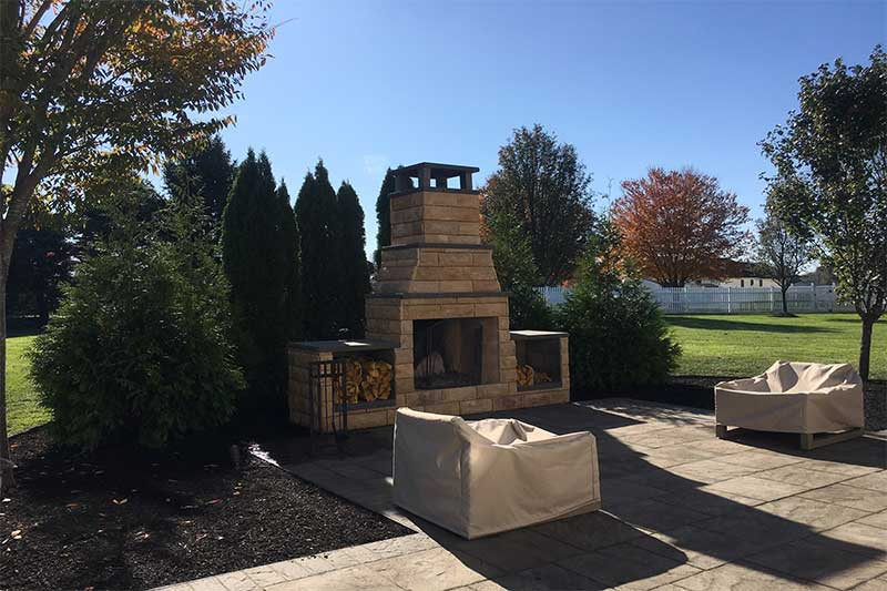 outdoor fireplace and patio with chairs